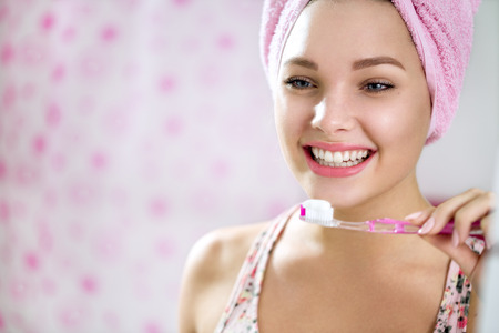 girl in towel: Smiling young girl brushing teeth in bathroom front of mirror Stock Photo