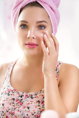 Young girl applying cream on face , skincare Stock Photo
