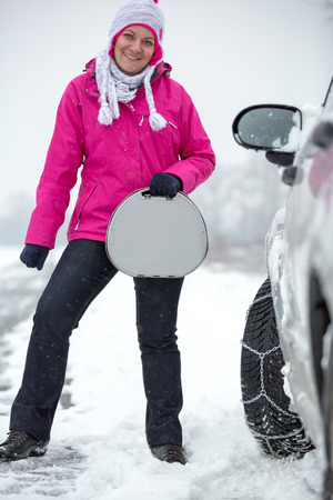 smiling woman standing next her car with snow chains on tire photo