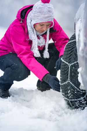 Young woman putting winter chains on car photo