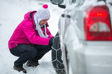 Winter, woman putting snow chains onto tyre of car photo