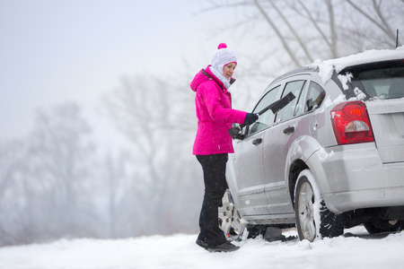 Young woman cleaning her car from snow photo