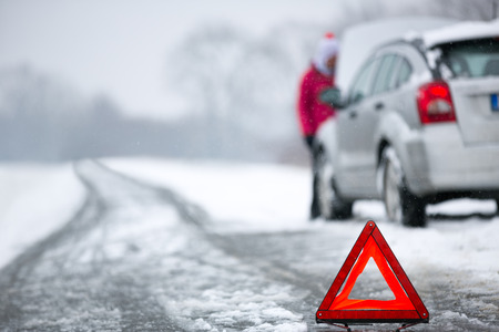 cars on the road: warning triangle with winter car breakdown in background