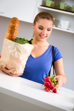 Young woman with groceries in shopping bag in kitchen photo