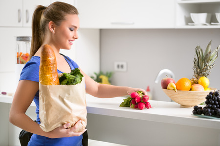 Woman  in kitchen holding a shopping bag full of fresh food photo