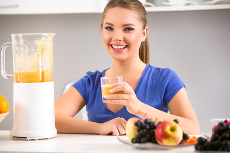 Beautiful woman using a blender with smoothie in the kitchen. photo