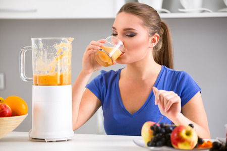 Young girl drinking tasty juice, healthy  fruits smoothies Imagens