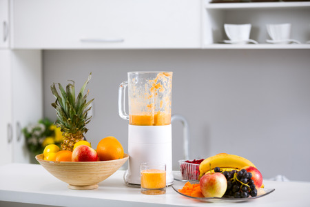 Prepared smoothies and healthy smoothie ingredients in blender with fresh fruit ready to blend on kitchen table photo