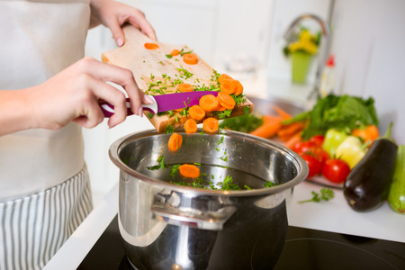 cocineros: Hortalizas frescas en la tabla de cortar están cayendo en la olla, el concepto de la cocina