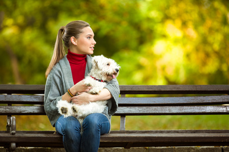 maltese dog: young woman hugging a maltese dog out in the park