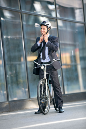 head protection: Businessman puts the bicycle helmet on head protection on bicycle