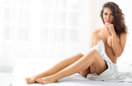seins nus: Sensuelle femme nue assise sur le lit