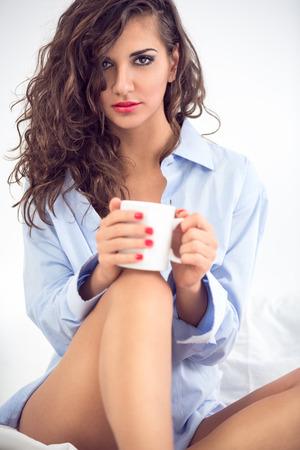 голая женщина: Привлекательная женщина с чашкой кофе в спальне Фото со стока