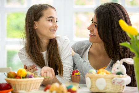 Happy mother and daughter preparing Easter eggs together photo