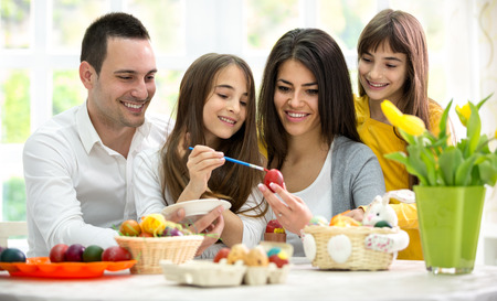coloring easter egg: Mother and father with daughters preparing eggs  for Easter Stock Photo