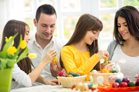 coloring easter egg: happy family on Easter, parent with two daughters playful with Easter eggs