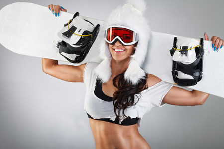 Cheerful girl posing with snowboard and fur hat