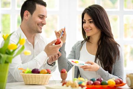 Jeune homme et la femme peignant des oeufs de Pâques, couple dans l'amour de Pâques
