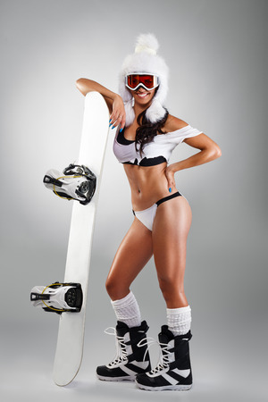 Sexy sportswoman with snowboard over grey background, full body photo