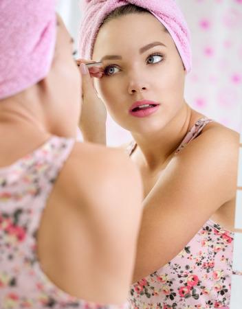 pinzas: joven y bella chica sacar las cejas con pinzas