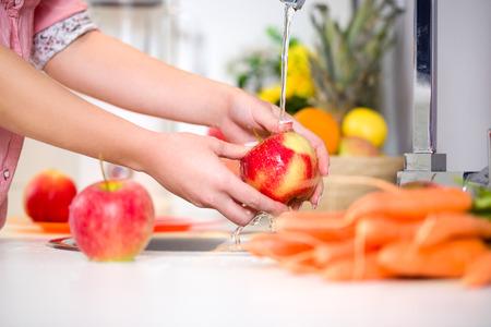 Kobieta ręce mycia smaczne jabłko pod kranem