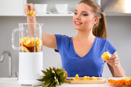 zumo verde: Jugos-mujer que hace el zumo de fruta usando la m�quina exprimidor en casa en la cocina