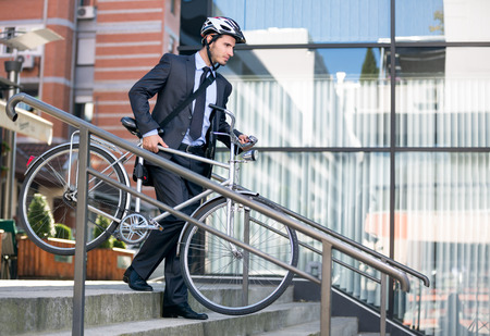 bicycle helmet: young businessman in crash helmet carrying bicycle down steps