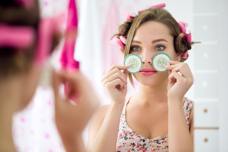 Young girl holding slice cucumber for eyes treatment front mirror