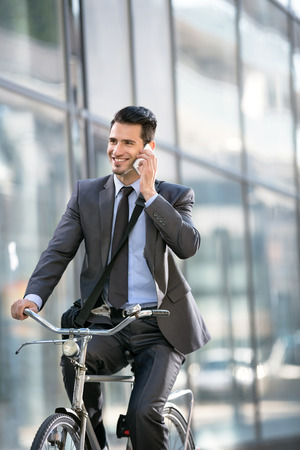 Young smiling business man with phone riding a bicycle by office building photo