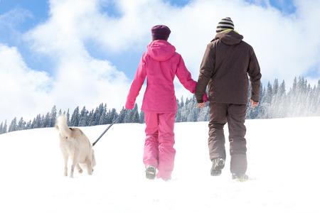 detras de: Hombre y mujer caminando con su perro en invierno, vista posterior