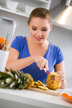 Young woman cutting fresh pineapple preparing juice photo