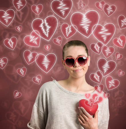 young woman holding broken heart photo