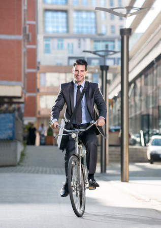 Man on a bicycle on modern city background, full length photo