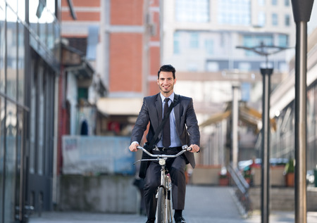 bicycles: Young businessman riding bicycle on street Stock Photo