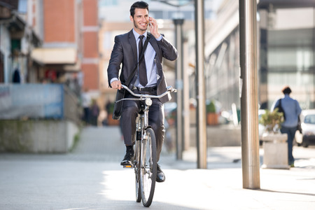 Young cheerful businessman riding a bicycle and using phone go to work photo