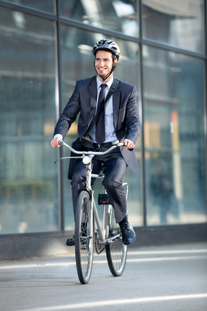 Young businessman riding bicycle by building  on street photo