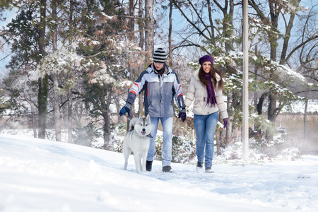 Young couple taking dog for a walk in snowwinter photo