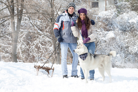 wolf couple: Happy young couple walking with dog snowy forest