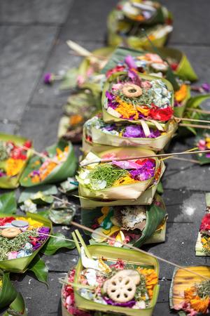 sacrificio: Ofrendas a los dioses balineses tradicionales en Bali con las flores y los palillos aromáticos