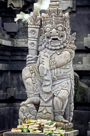 offerings: Statues and carvings depicting demons or gods with offerings in Ubud, Bali. Stock Photo