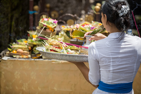 Balinese  woman carrying offering to local temple in Bali, Indonesia. Offering flowers and other gifts is very popular tradition on Bali. Stock Photo