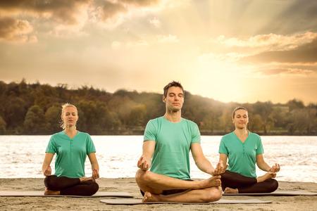 mujer meditando: Grupo de hombres serenos meditando en la naturaleza Foto de archivo