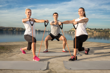 rubber bands: Active people exercising with a resistance band outdoor Stock Photo