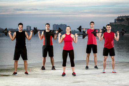 body pump: muscular young people doing exercise with weights, outdoor Stock Photo