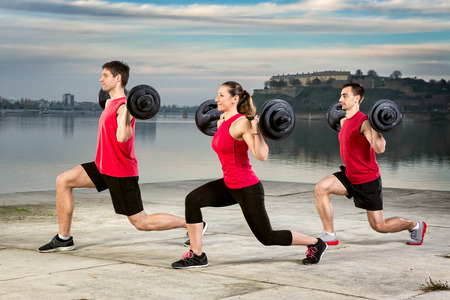 group of young people picking up barbell weight photo