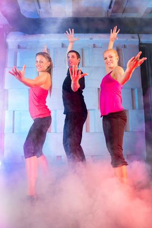 Grupo de jóvenes bailarines sobre fondo de discoteca