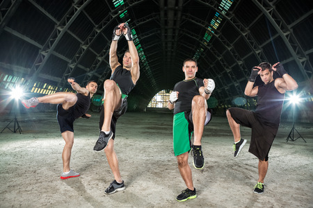 modern fighter: Four men practicing kick box, making hit with legs Stock Photo
