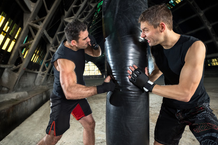 sandbag: boxer man during boxing hitting heavy bag at training