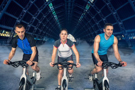 spins: group of three people exercise on bike, spinning class,