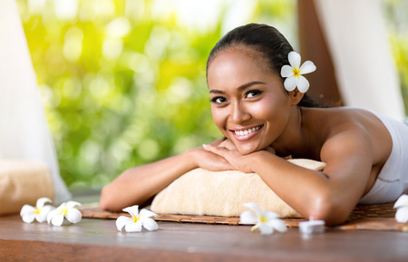 Beautiful smiling woman relaxing under canopies for massage Stock Photo